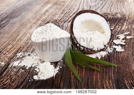 Fresh coconut flour raw coconut half on wooden table. Healthy coconut eating.