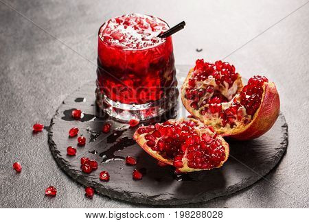 A close-up of a colorful alcohol drink with garnet juice, ice and black straw. A raw and tasteful pomegranate and a glass of red juice on a light gray background. Delicious garnet products on a tray.