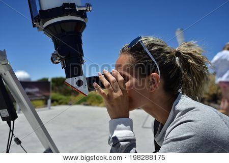 woman tourist looking through big telescope at astronomic observer on Teide peak, Tenerife - Spain