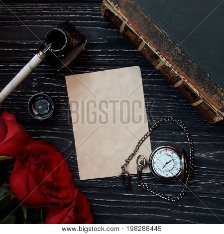 Beautiful vintage background (sheet of paper three red roses dip pen with an ink-pot ancient book and an antique pocket watch with a heart-shaped chain on a worn black wooden background)