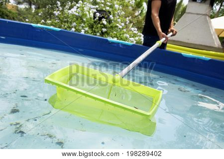 closeup of a young caucasian man cleaning the water of a portable swimming pool placed in the backyard with a leaf skimmer mounted in a telescopic pole