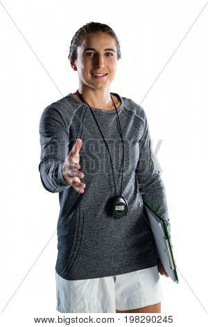 Portrait of female rugby coach extending arm for handshake while standing against white backgrond