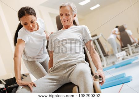 Strong legs. Attentive brunette standing behind her patient and bowing her head while massaging injured leg