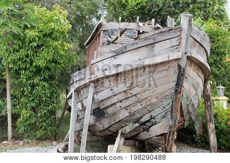 An Old Wooden Fishing Boat In Garden As Decoration Item