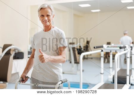 Cheer up. Positive pensioner keeping smile on his face and feeling happiness while posing on camera