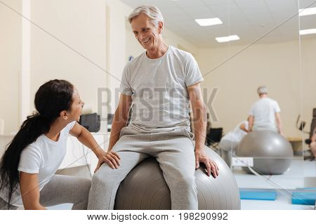 My sport equipment. Handsome invalid male person sitting on big fitness ball and expressing positivity while showing his smile