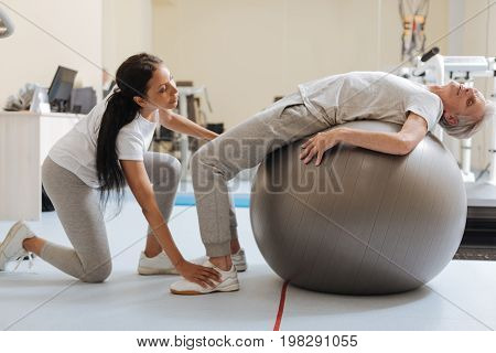 Just relax. Attentive female person working as coach that keeping legs of her visitor while helping to rehabilitate after operation