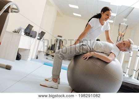 Fitness for everybody. Serious mature man pressing lips while raising head and lying on fitness ball