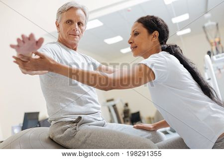 Follow me. Competent instructor expressing positivity while helping her patient and holding his hands