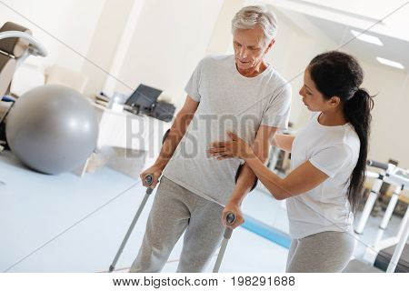 Be slowly. Injured mature male person looking downwards and using sticks while trying to walk in the gym