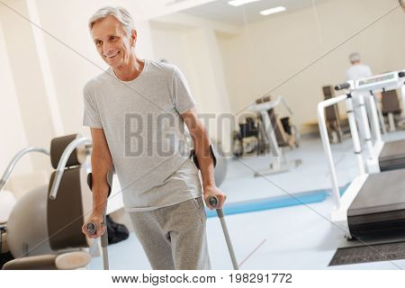 I can walk. Handsome pensioner expressing positivity and leaning on crutches while looking forward