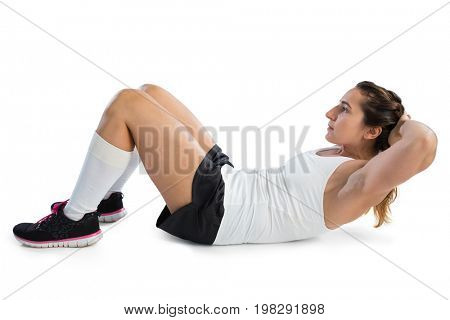 Side view of female athlete practicing sit ups against white background