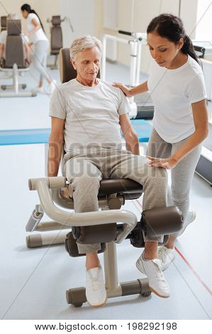 Listening recommendations. Serious pensioner bowing head while looking downwards and sitting on the training device