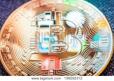 closeup of golden bitcoin coin with a smartphone display aplications reflection on its surface