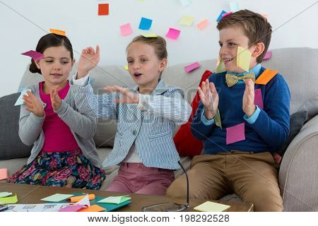 Kids as business executives playing with sticky notes in office