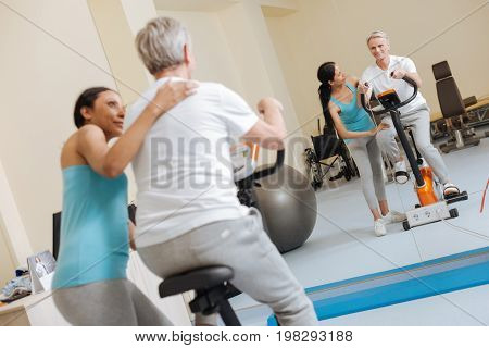 Work at your body. Attentive woman standing behind her client and putting her hand on his shoulder while supporting him