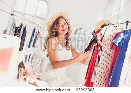 The young pretty girl choosing and trying on Model shoes at shop. Concept of shopping