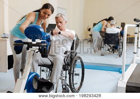 Health in sport. Disabled mature man being very attentive while training and sitting on his wheelchair