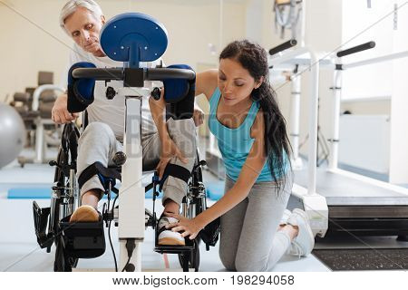 Fix it. Serious trainer standing near her patient and keeping her hands on his leg while looking downwards