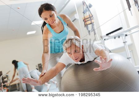 Do it carefully. Delighted brunette keeping smile on her face and bowing head while helping her patient