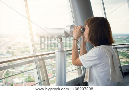 Young woman using binoculars for city view scape and birdwatching.