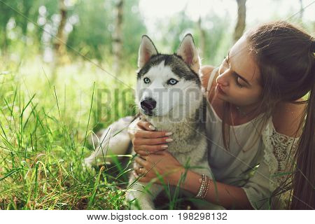 A portrait of beautiful girl keeping pretty white husky dog outdoor