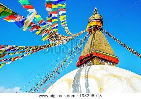 Bodhnath stupa in kathmandu with buddha eyes and prayer flags on clear Blue sky background.