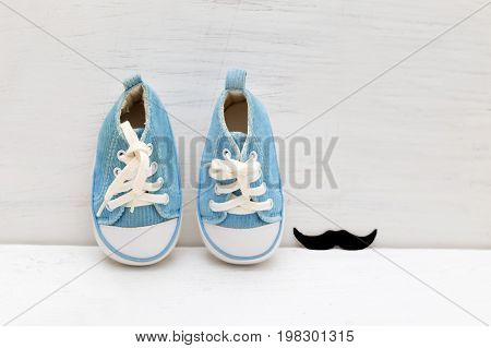 Little baby blue sneakers for boy and mustaches on a white wooden background
