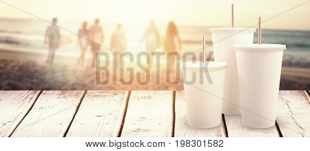White cups over white background against happy friends walking with surfboards