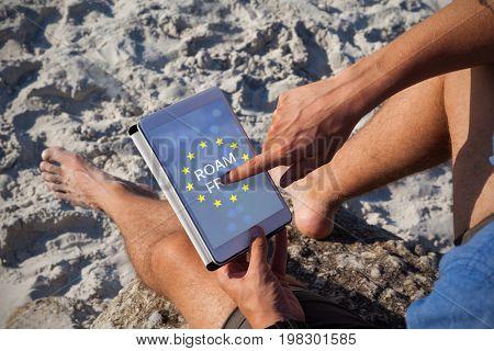 Roam free text on European Union flag against man using digital tablet on the beach