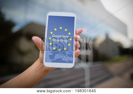 Good bye roaming text on European Union flag against woman holding mobile phone
