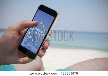 Good bye roaming text on European Union flag against close up of man using smartphone at beach