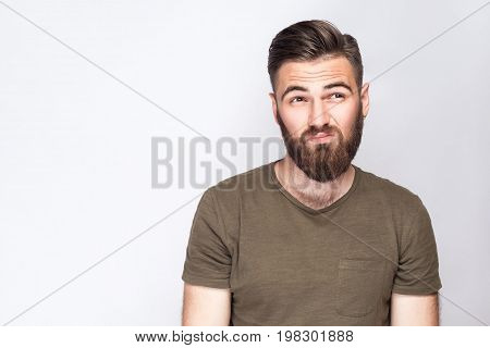 Portrait of thoughtful bearded man with dark green t shirt against light gray background. studio shot.