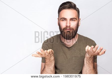 I don't know! Portrait of confused bearded man with dark green t shirt against light gray background. studio shot.