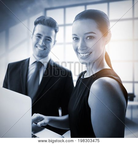 Business people standing with a laptop against interior of empty office