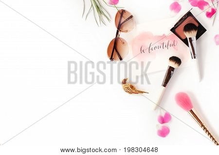 Top View Of Cosmetics And Female Accessories On White With Pink Petals And Inspirational Words Writt