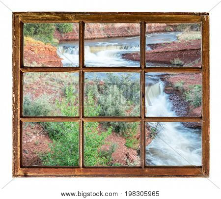 creek with waterfalls in northern Colorado foothills as seen through a vintage sash window