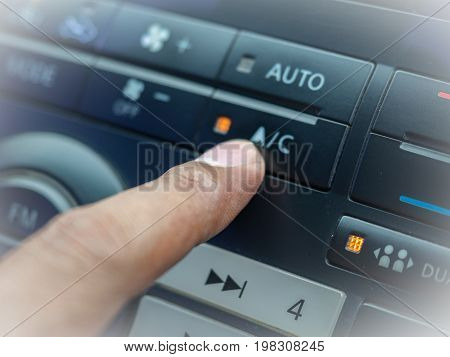 Car's driver pressing control button on panel