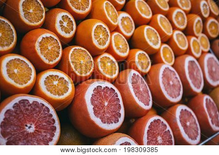 Rows of ripe juicy cut oranges and grapefruits on the market