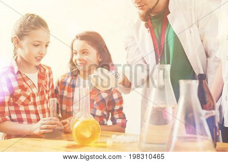 Give it to me. Attentive girl standing in semi position near her cousin and keeping mouth opened while holding flask with reagent in right hand