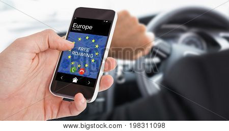 Cropped hand of man using smartphone against businessman in the drivers seat
