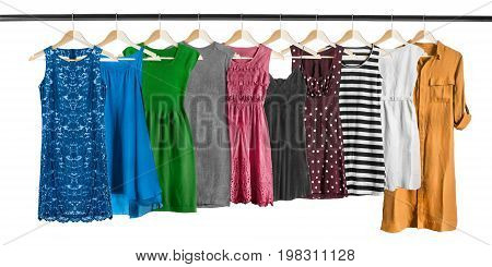 Set of elegant dresses on clothes racks on white background
