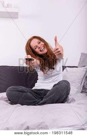 Young red-haired woman with the remote control in her hand watching television