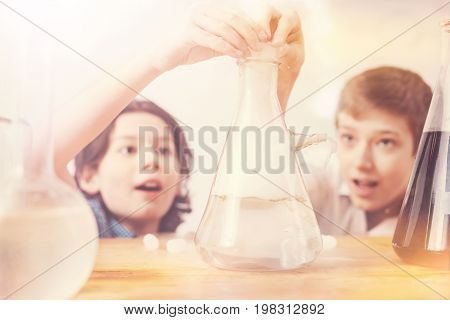 Interested in process. Close up of interesting bottle that standing on the table and being used in experiment