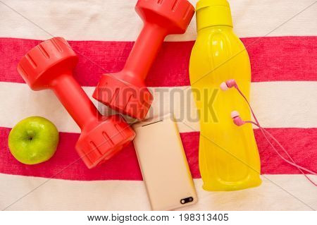 Athlete's set with two pink dumbbells, smarphone with pink headphones, green appple and a yellow bottle of water, over a white and pink towel.