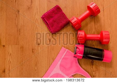 Athlete's set with female clothing, red small towell, two pink dumbbells, bottle of water and a pink sport bra on wooden background.