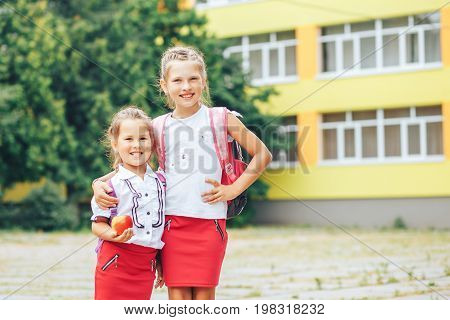Two cute sisters go to school. The elder sister leads the youngest first time in the first class. Back to school.