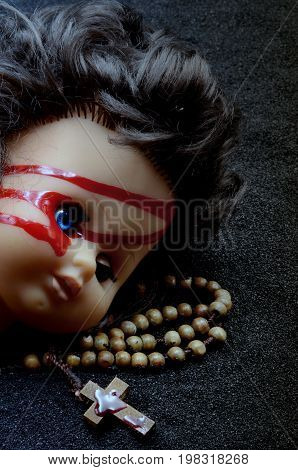Doll head with cross on black sand photo