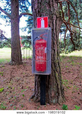 A fire extinguisher attached to a side of a tree