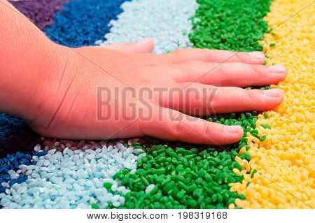 color and tactile therapy. a child's hand touches the colored rice